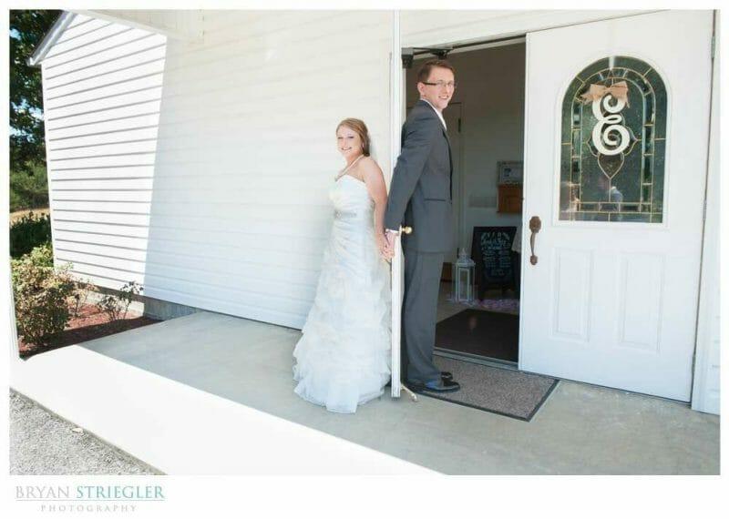Arkansas Wedding couple holding hands around door