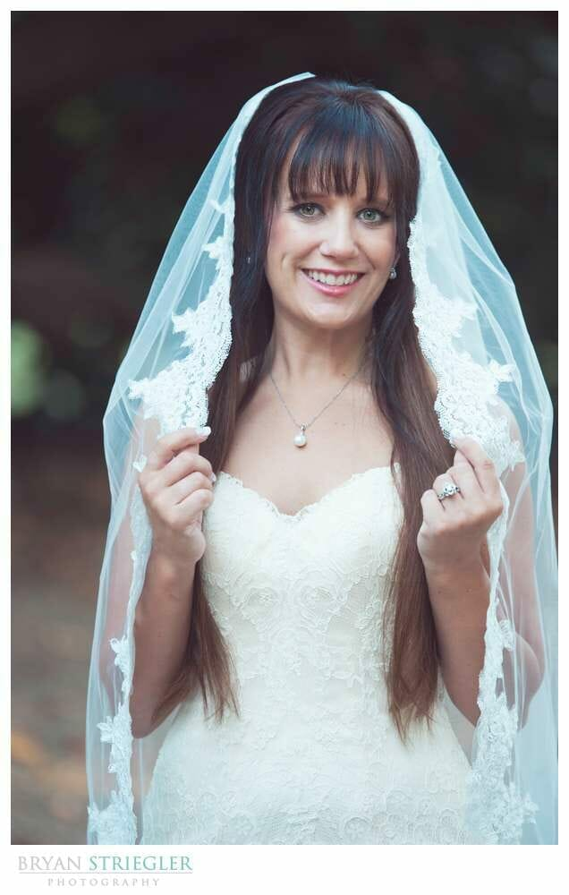 Ashley's Arkansas Bridal Portraits at Magnolia Gardens holding veil