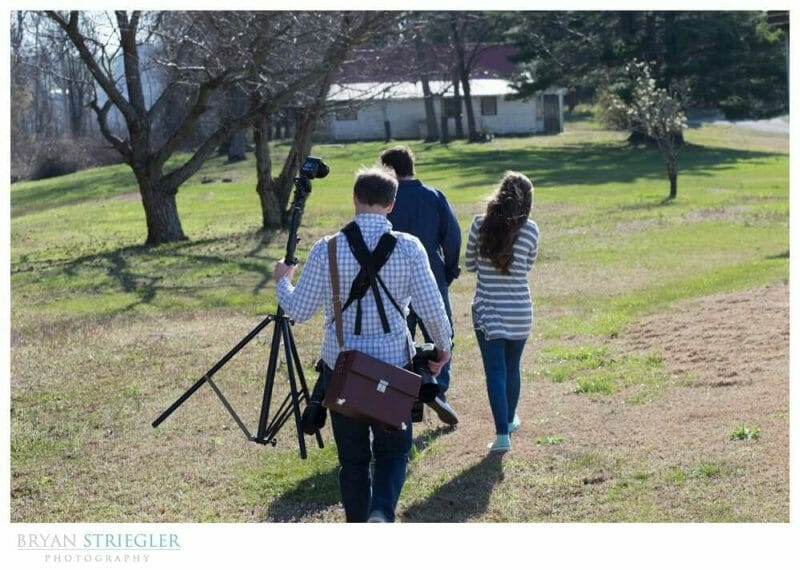 Having a Wedding Photography assistant carrying lightstand