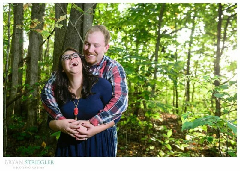 Engagement photos laughing in the woods