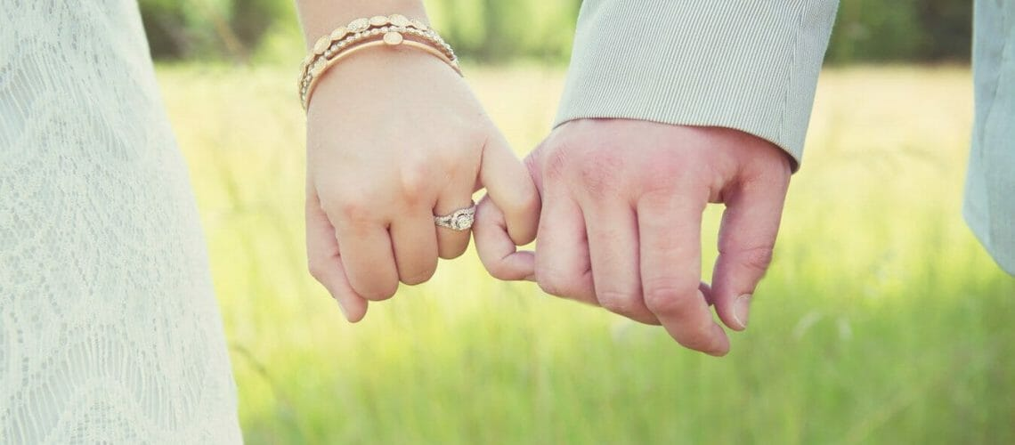 Up close of wedding ring and holding hands