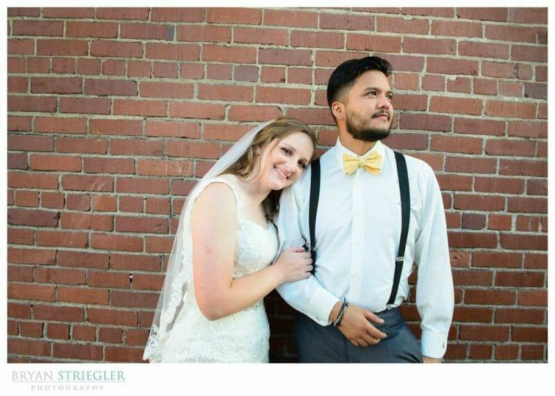 couple portrait against brick wall