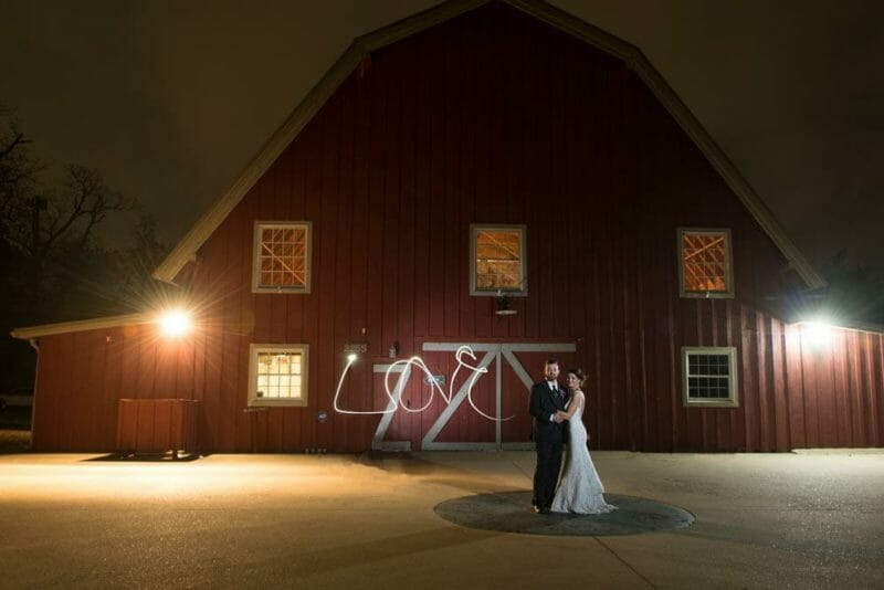 bride and groom in front of Pratt Place Barn