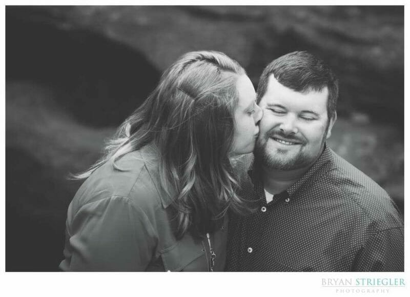 Black and white engagement photo of kissing
