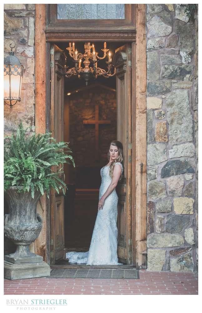 Bride leaning against doors at Matt Lane Farm