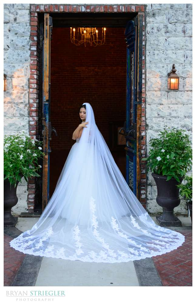 Bride with veil in front of entrance to the Ravington