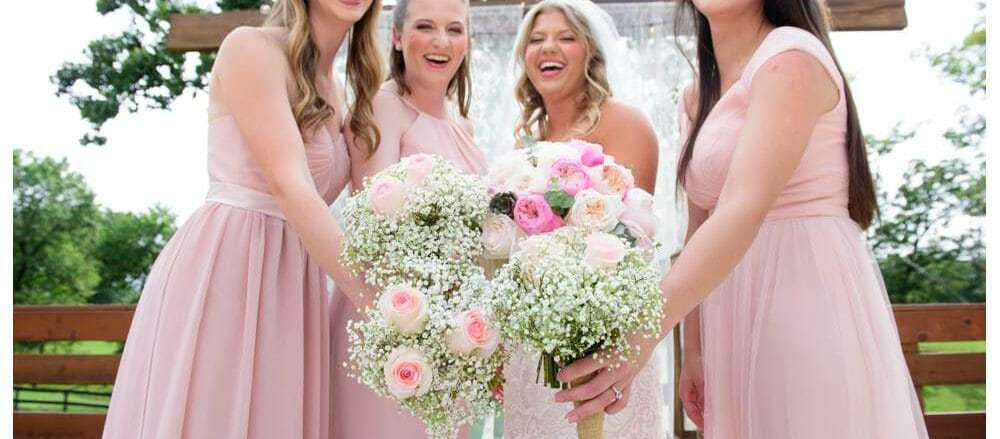 bridesmaids laughing and putting together bouquets