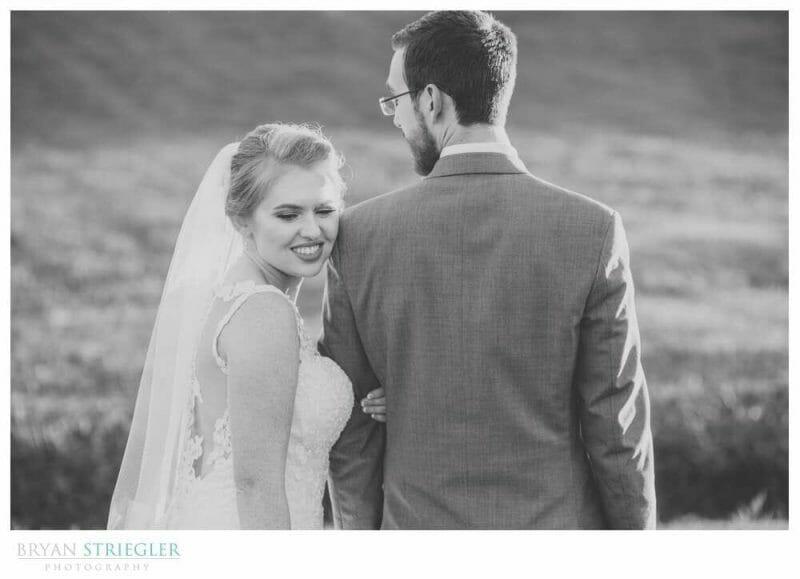 bride looking over groom's shoulder