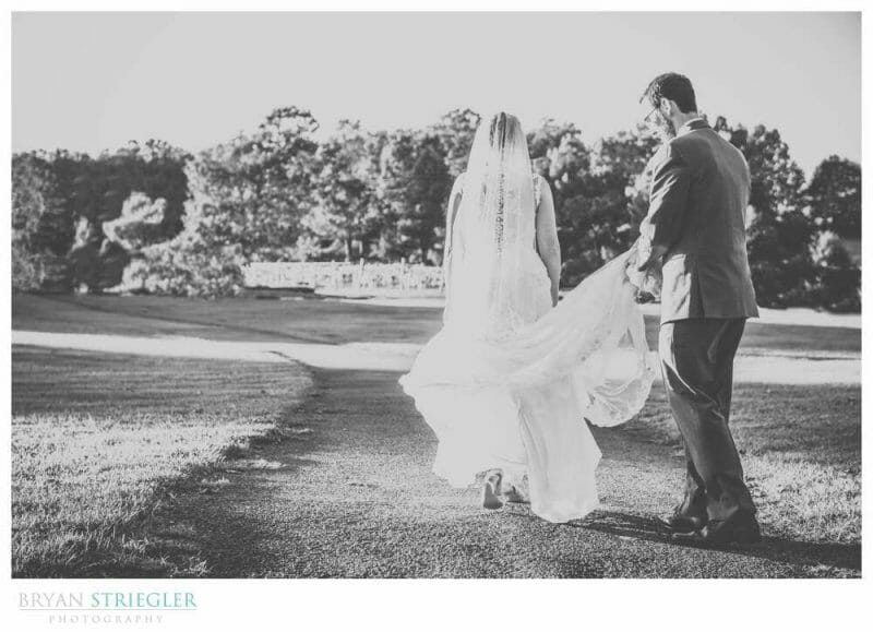 groom holding her dress while walking