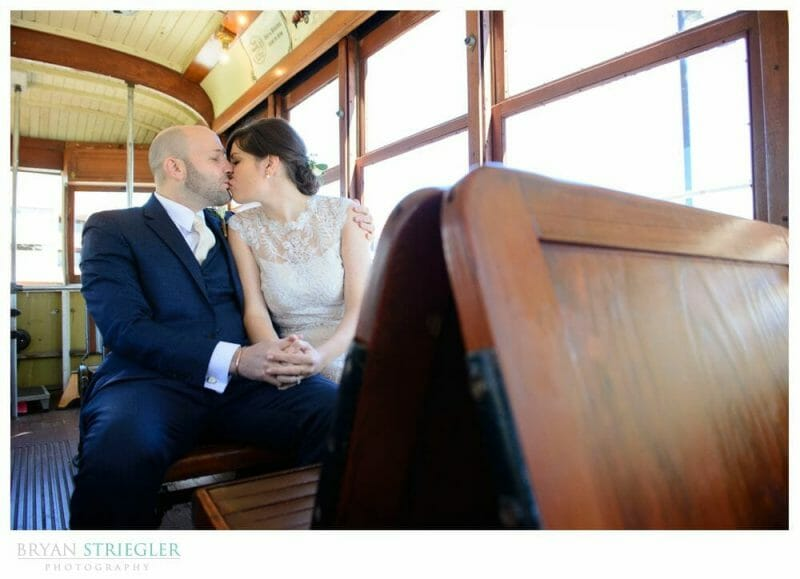 bride and groom kissing in trolley