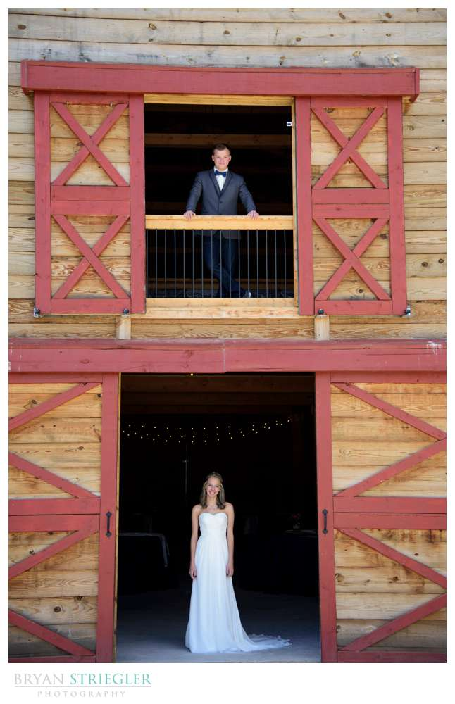 bride and groom on different levels of barn