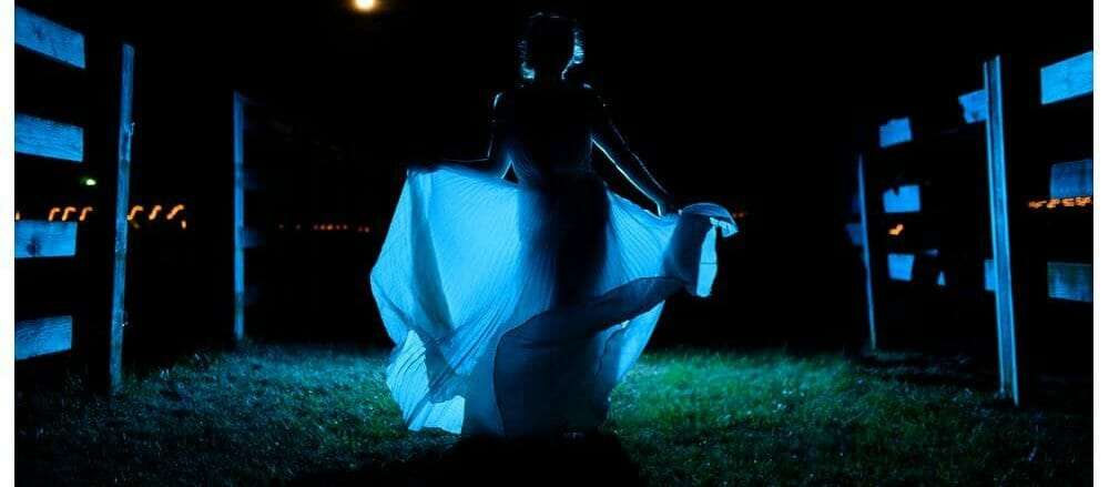 Dramatic photo of bride dancing at night with a full moon