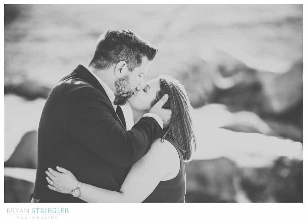kissing by creek engagement photo