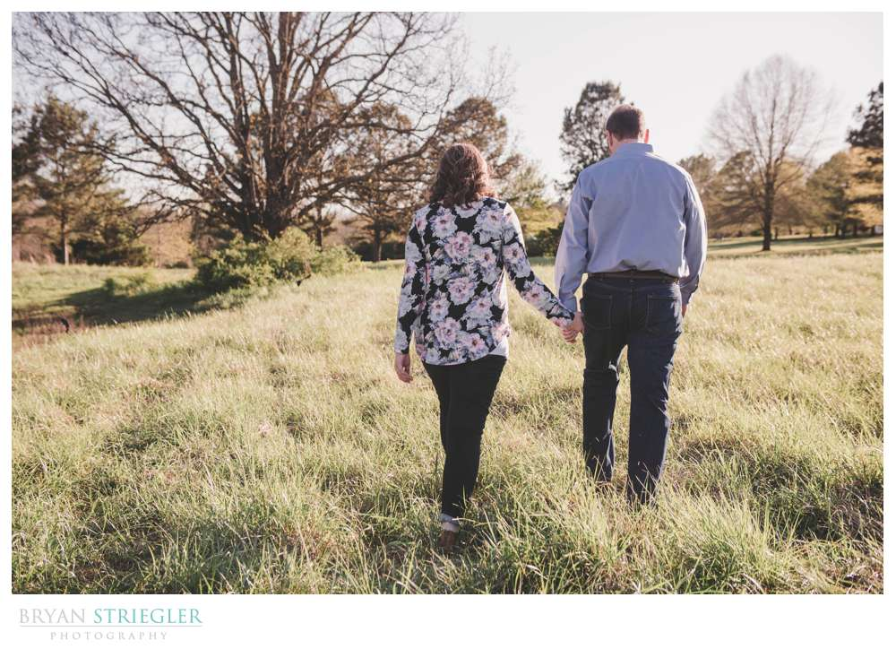 walking through a field during engagement session