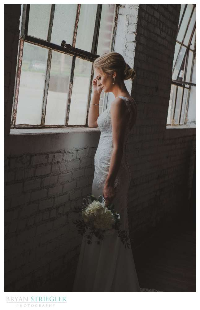bride posing in front of large window