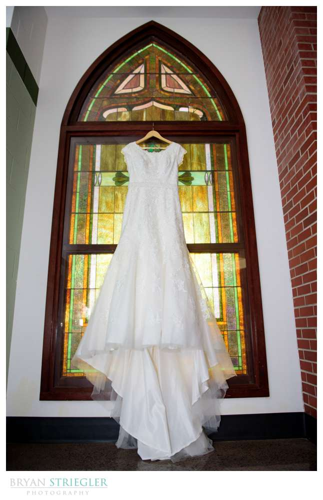 wedding dress hanging in front of stained glass