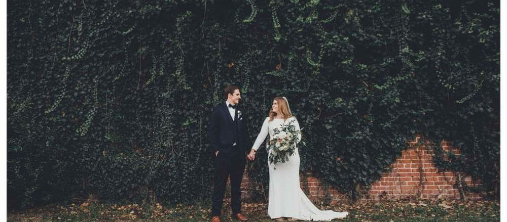 wedding couple in front of giant ivy wall