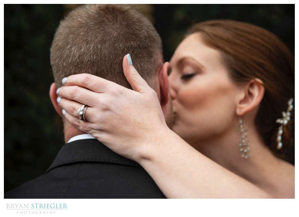 close up of wedding ring with bride kissing groom