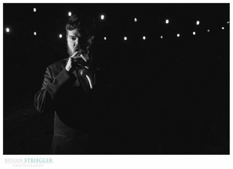 dramatic black and white of groom smoking