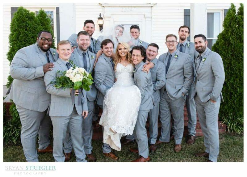 guys lifting up bride