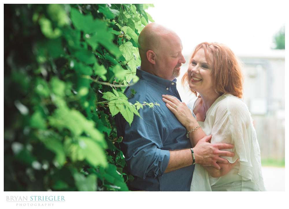 couple against a vine covered wall