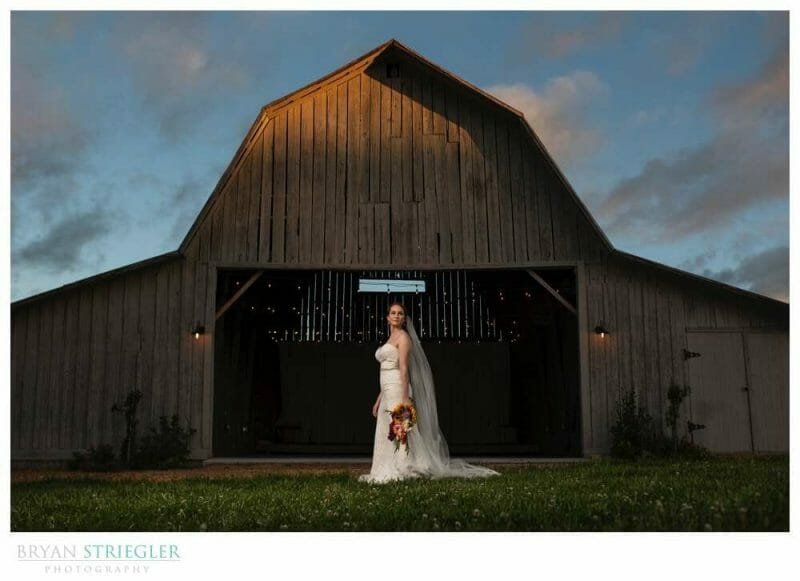 bride in front of Old Gray Barn
