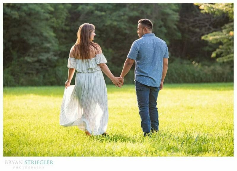 engagement photo walking through a field