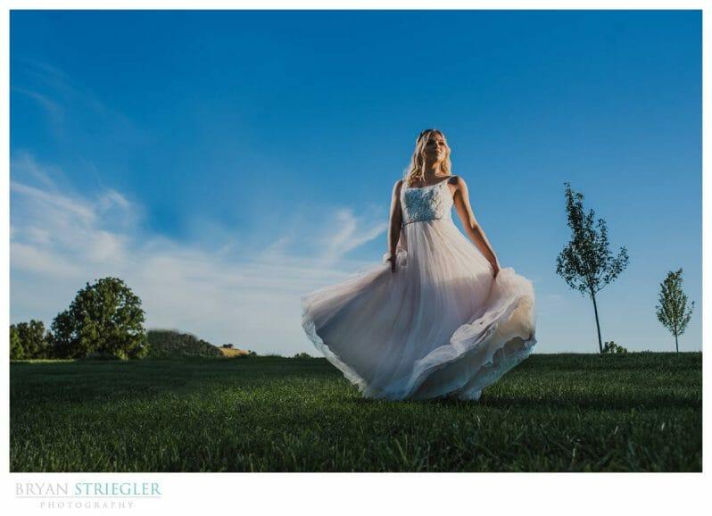 bride swirling dress with blue sky