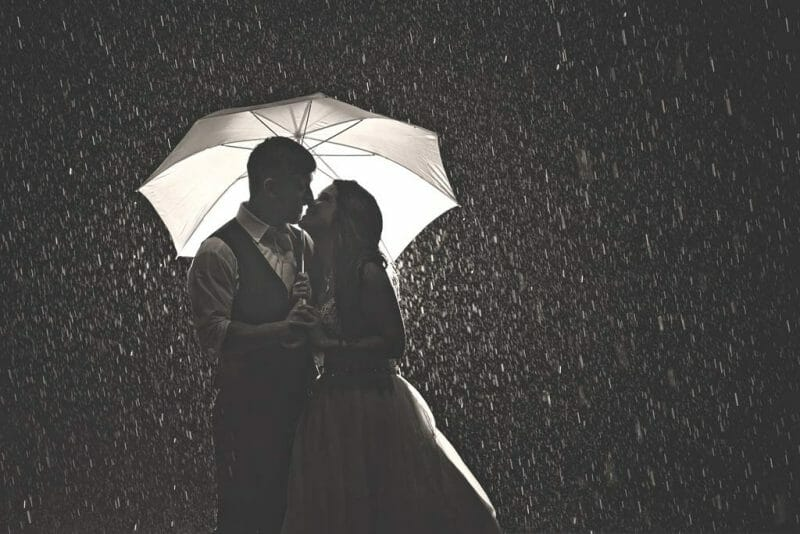 bride and groom in rainstorm holding umbrella and black and white