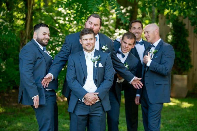 groomsmen acting silly behind groom's back