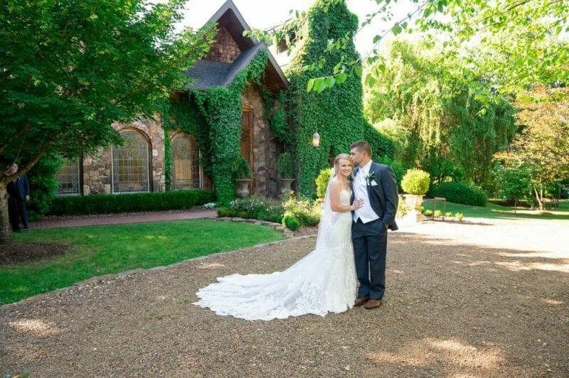 bride and groom kissing in front of Matt Lane Farm