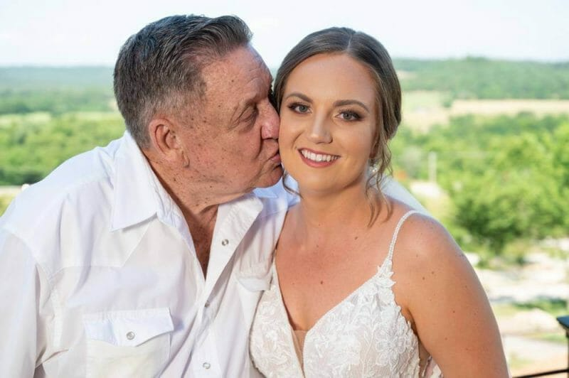 bride being kissed by grandfather