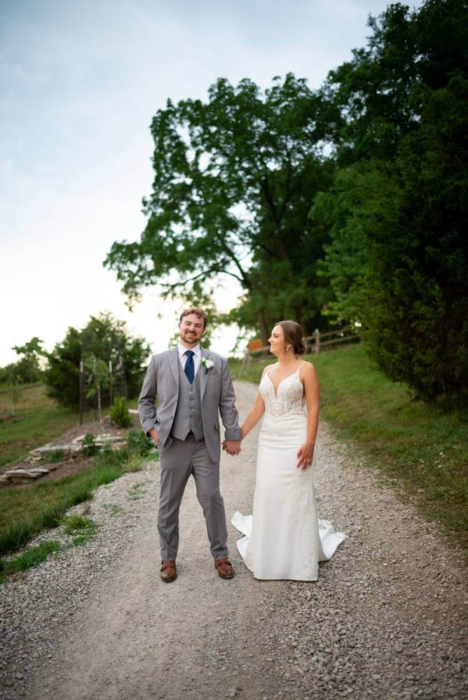 wide shot of bride and groom on gravel path