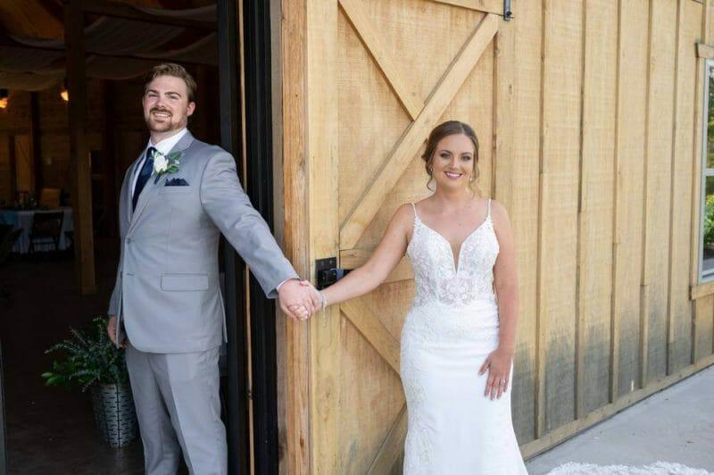 wedding couple holding hands around door