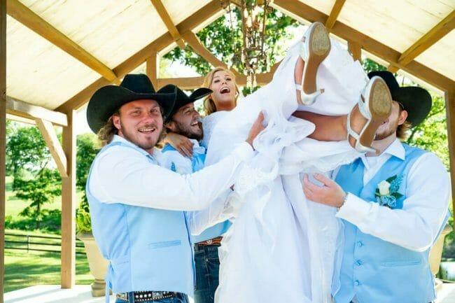 groomsmen tossing bride in the air