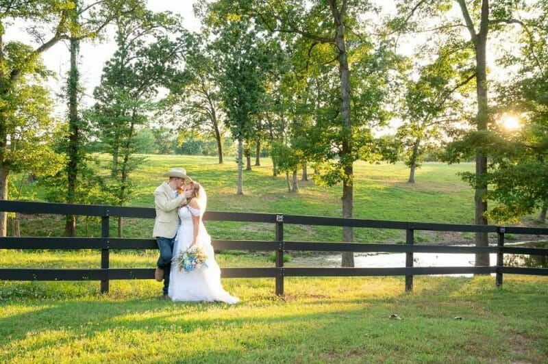 wide shot of bride and groom against a fence with sunset