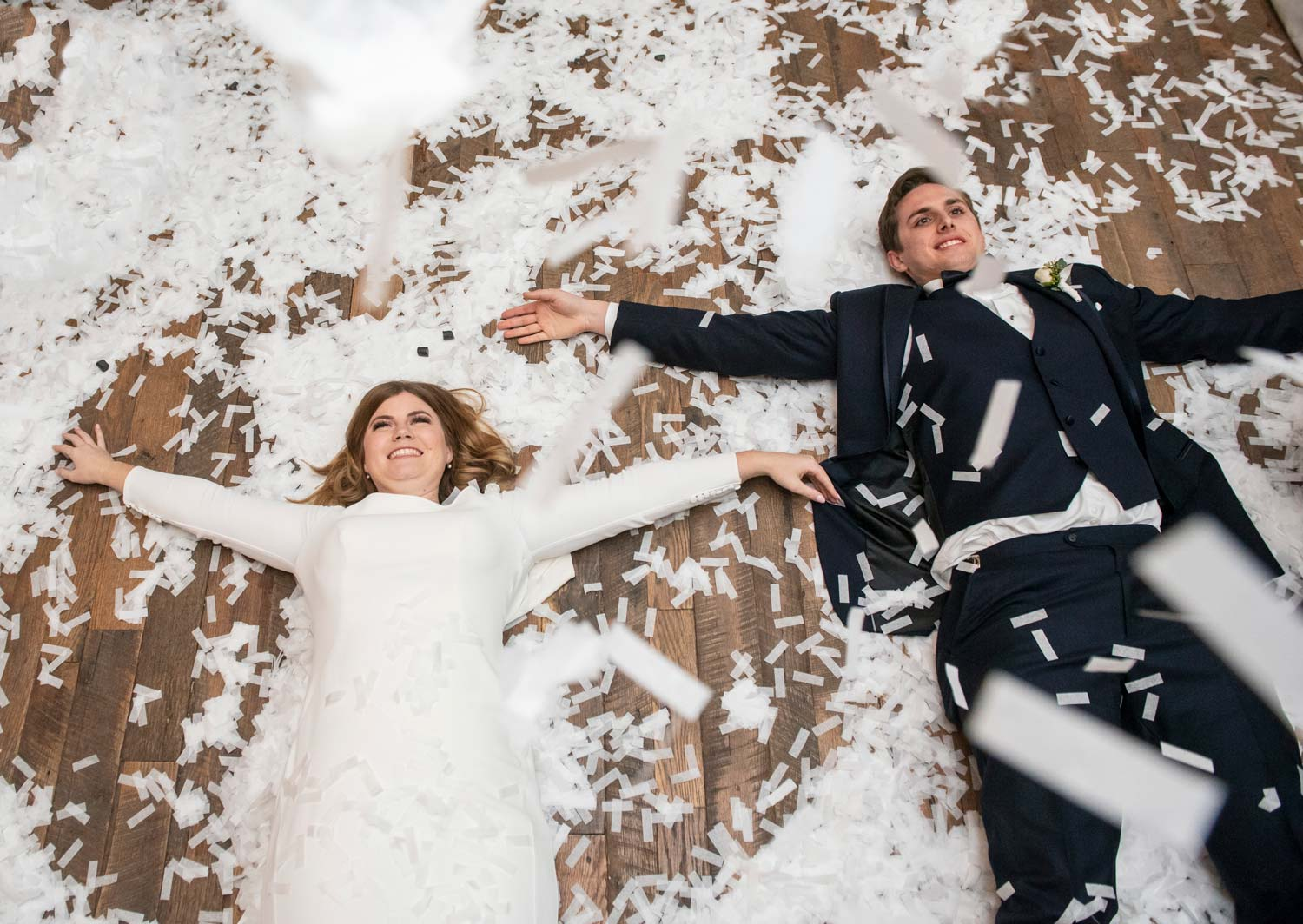 bride and groom making snow angels in confetti