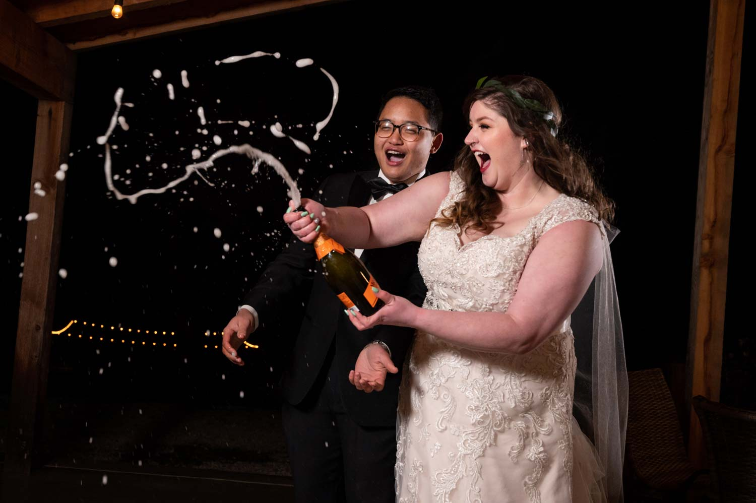 bride and groom spraying champagne at wedding