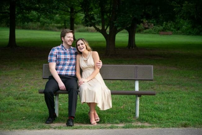 engagement photo in park sitting on bench