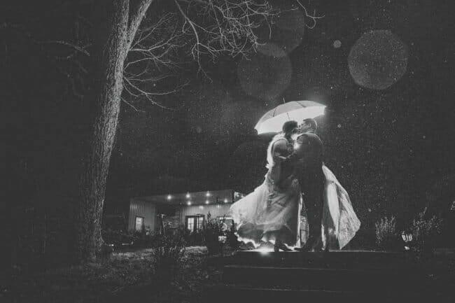 black and white wedding rain photo with umbrella