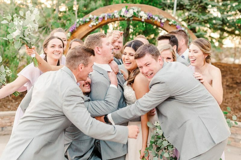 bridal party running and hugging couple