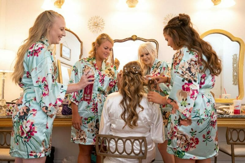 bridesmaids helping bride with hair