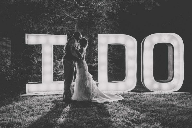 couple in front of light sign