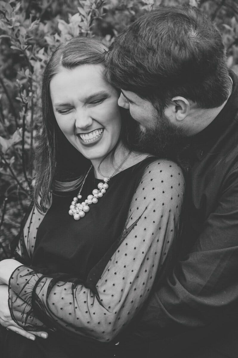 black and white of engaged couple laughing