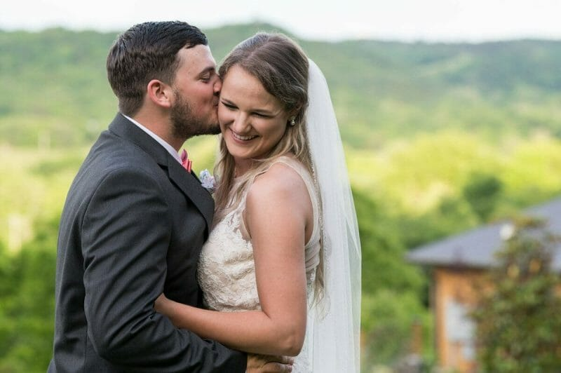 bride laughing while groom kisses