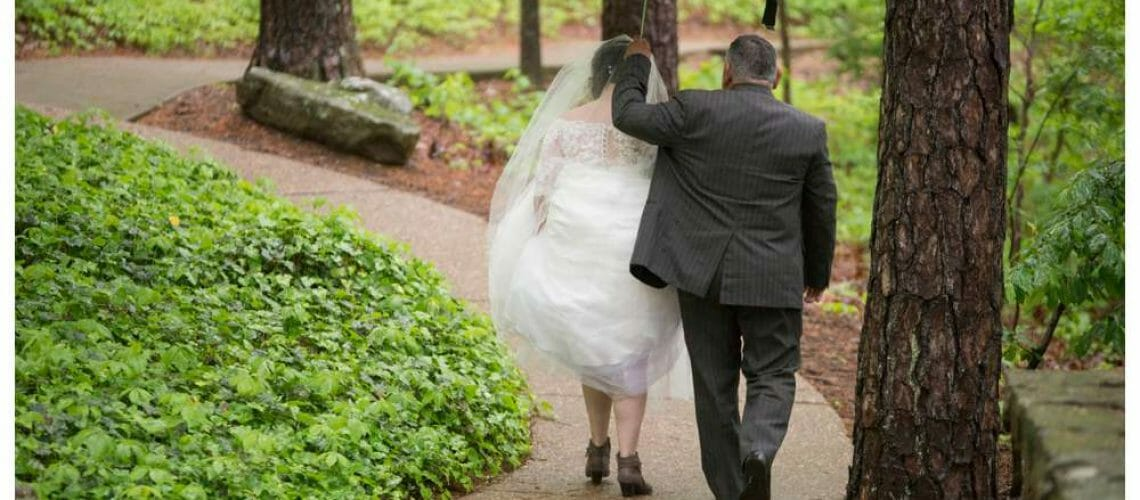 father walking bride in the rain with an umbrella