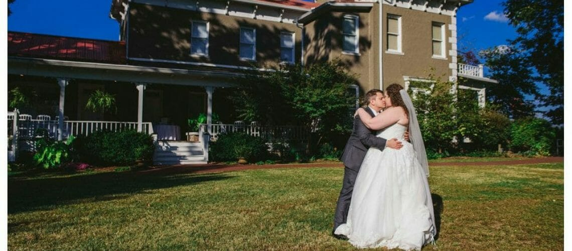 bride and groom kissing in front of Peel Mansion
