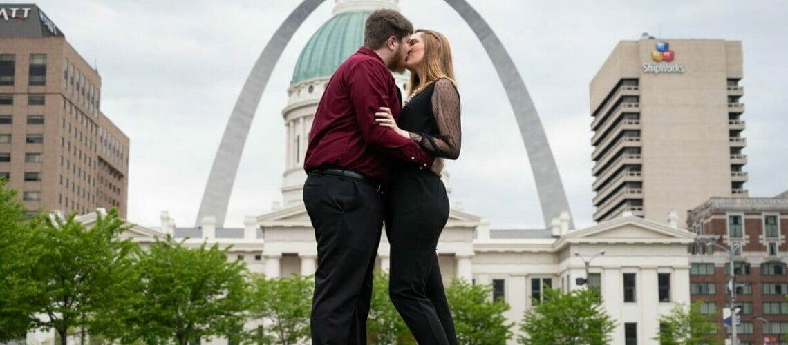 wide shot of couple with St. Louis arch and old courthouse