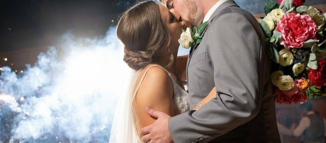bride and groom kissing with smoke in background from sparklers